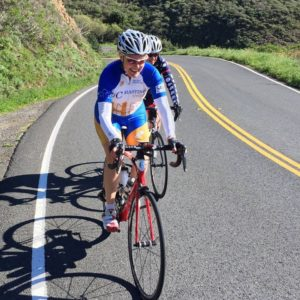 skilled bicyclist riding on winding road in California, to visit her law office contact the leading Alameda Injury Law office.