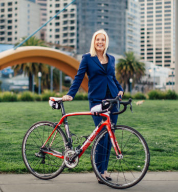 A highly trained San Francisco pedestrian accident attorney standing in a park with a bike.