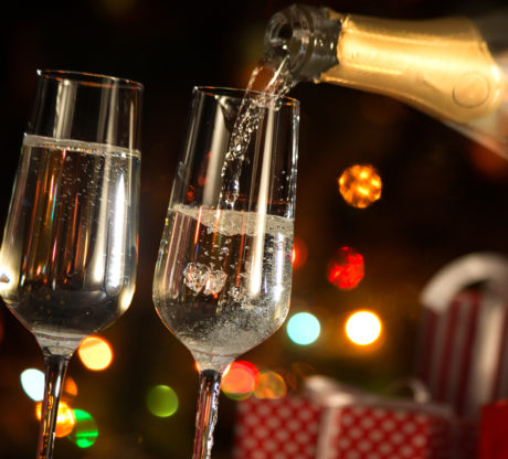 Champagne glasses with presents and Christmas lights in background, if you have been injured from a car accident involving a drunk driver meet with our Bay Area Car Accident Lawyer.