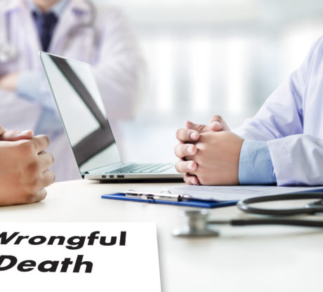 """Doctors sitting at a table with a laptop and some paperwork that says """"Wrongfull Death"""", representing how one can benefit from contacting a San Francisco wrongful death attorney."""