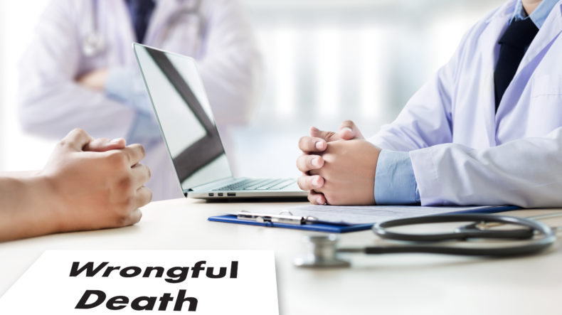 "Doctors sitting at a table with a laptop and some paperwork that says ""Wrongfull Death"", representing how one can benefit from contacting a San Francisco wrongful death attorney."