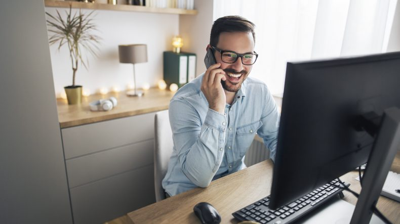 Man smiling at his computer on the phone. He is on the phone with an experienced Bay Area injury attorney.