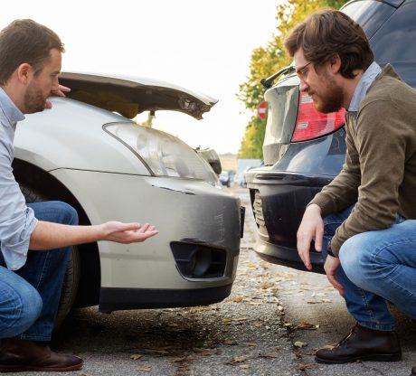 Two men kneeling by a car accident discussing the accident before contacting a Bay Area car accident attorney.