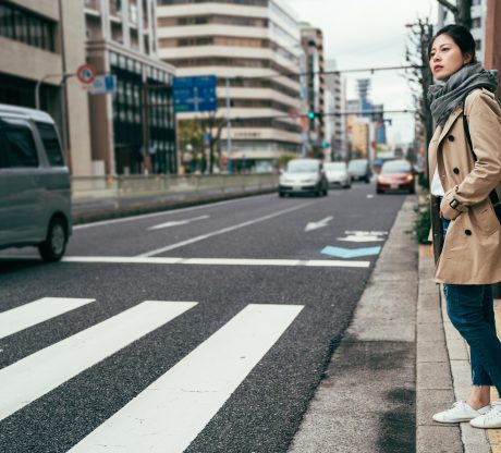 A woman in a jacket prepares to walk across a buys street after speaking with our San Francisco pedestrian accident attorneys.