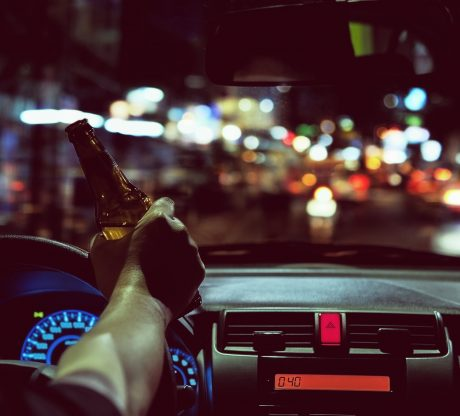 A man is drinking a beer behind the wheel. If you or a loved one have been injured, talk to a San Francisco car accident lawyer today.