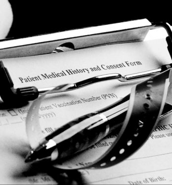 A patient medical document on a clipboard with a hospital bracelet and a pen on top of it representing how you can benefit from speaking with a San Francisco wrongful death lawyer.