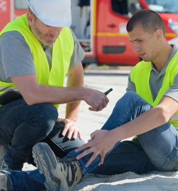 Two construction workers, one with an injured ankle, kneeling on the ground before contacting a Bay Area workplace injury attorney.